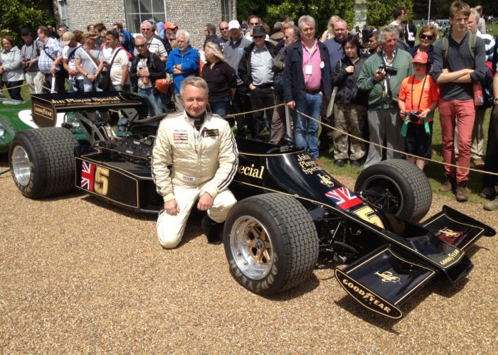 Checkered Past Racing's Chris Locke poses with Chekered Past Racing's 1976 Lotus 77 at The Goodwood Festival of Speed